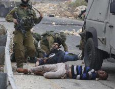 Soldados israelíes detienen a manifestantes palestinos durante la escalada de violencia que ha tenido lugar en Israel. (Foto Prensa Libre: AFP).