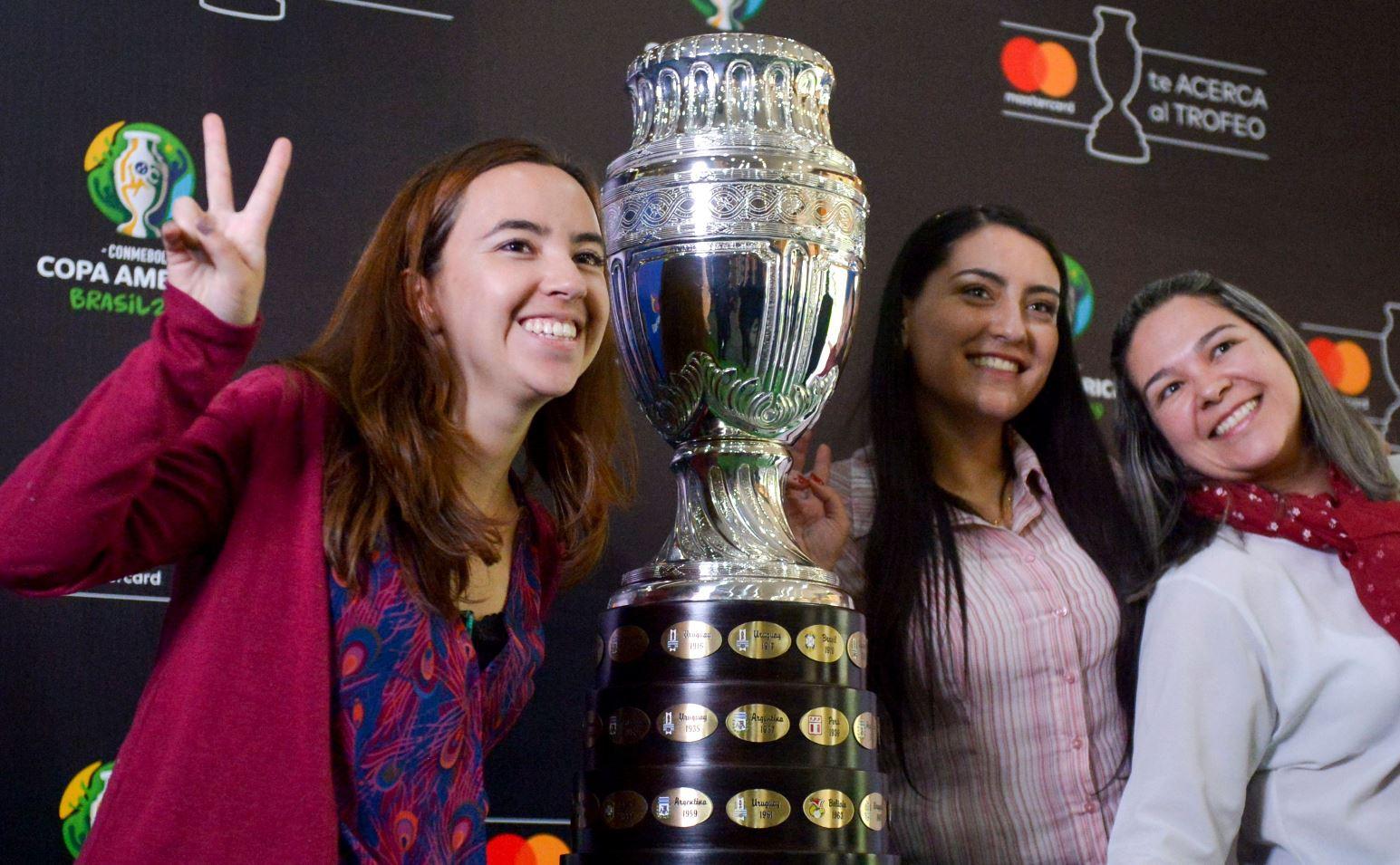 Varias aficionadas posan junto al trofeo de la  Copa América en Bogotá. (Foto Prensa Libre: AFP).