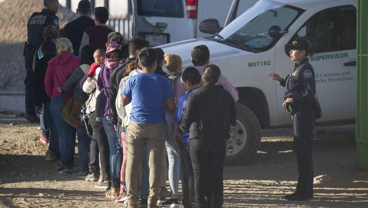 Migrantes esperan abordar un bus para presentar su solicitud de asilo a las autoridades estadounidenses en El Paso, Texas. (Foto Prensa Libre: AFP)