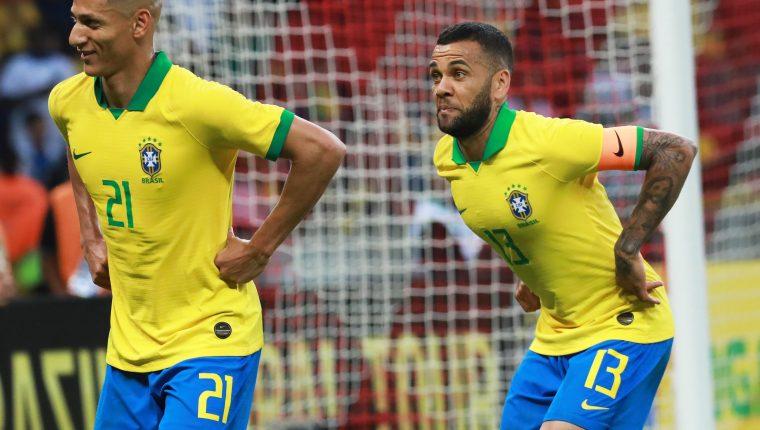 Richarlison (i) y Dani Alves (d) de Brasil celebran una anotación ante Honduras, este domingo, durante un partido amistoso internacional entre la selecciones de Brasil y Honduras celebrado en el Estadio Beira-Rio de Porto Alegre (Brasil).  (Foto Prensa Libre: EFE)