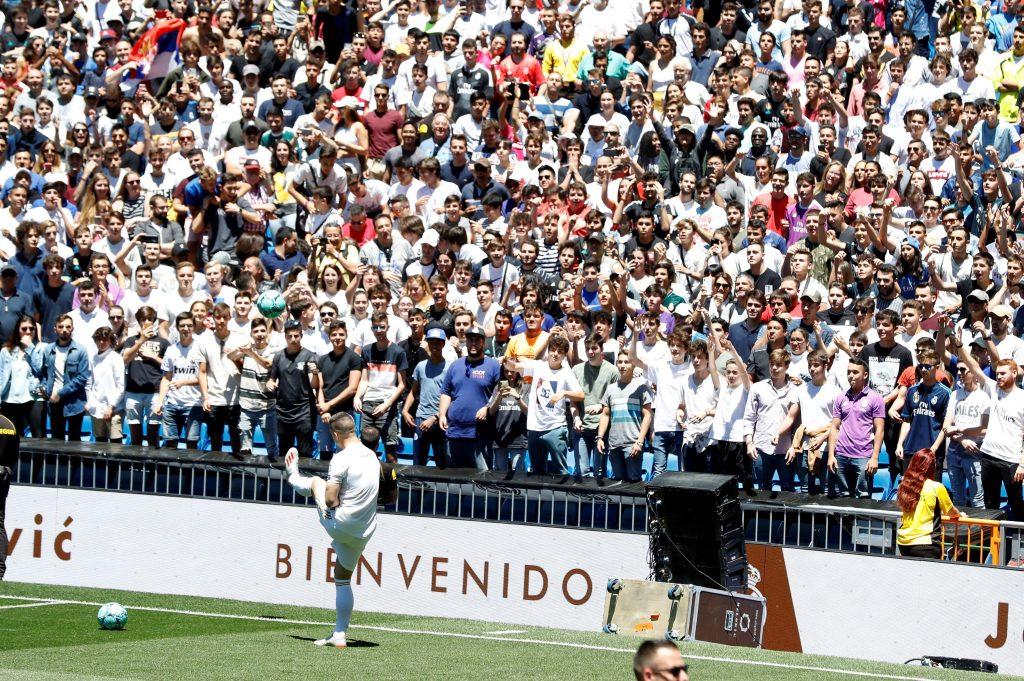 Luka Jovic con la camiseta del Real Madrid en el cesped del estadio Santiago Bernabeu donde acudieron numerosos aficionados tras su presentación como nuevo jugador del club blanco.  (Foto Prensa Libre: EFE)