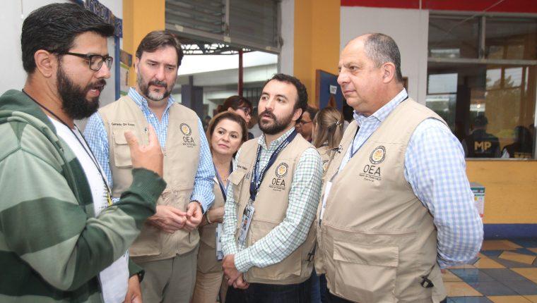 El jefe de la misión electoral de la Organización de los Estados Americanos (OEA), el expresidente costarricense Luis Guillermo Solís (d), en una visita a un colegio electoral. (Foto Prensa Libre: EFE)