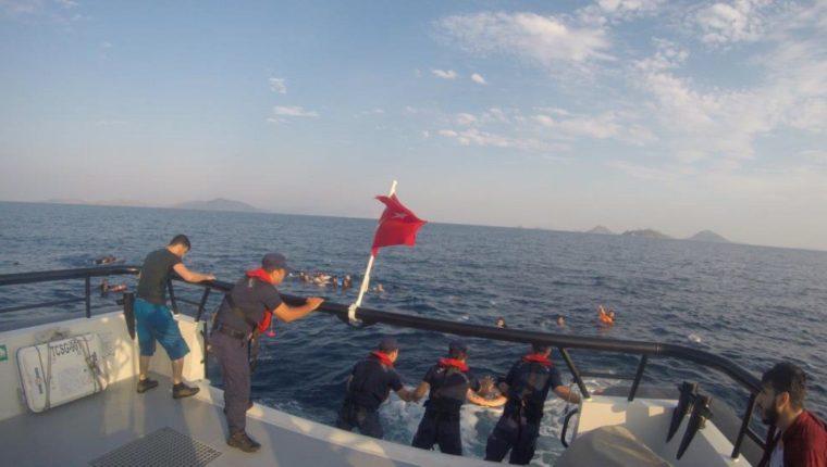 Un barco turco rescata a migrantes quienes viajaban en una embarcación que se hundió en el mar Egeo. (Foto Prensa Libre: EFE)