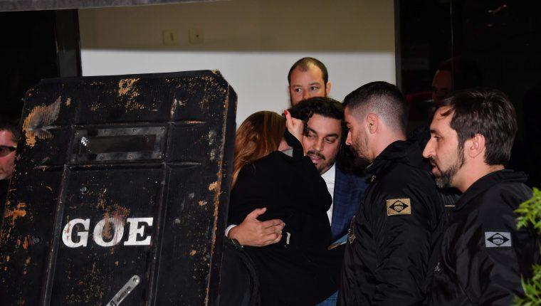 Najila Trindade Mendes de Souza es cargada por su abogado Danilo Garcia de Andrade después del interrogatorio con la policía. (Foto Prensa Libre: AFP)