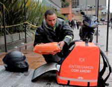 """Un mensajero en bicicleta que trabaja para la empresa colombiana de entrega en línea """"Rappi"""", organiza un pedido en Bogotá,. (Foto Prensa Libre: AFP)"""