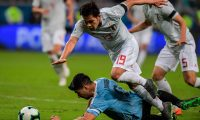 Japan's Tomoki Iwata(top) and Uruguay's Luis Suarez battle for the ball during the Copa America football tournament Group C match at the Gremio Arena Stadium in Porto Alegre, Brazil, on June 20, 2019. (Photo by Carl DE SOUZA / AFP)