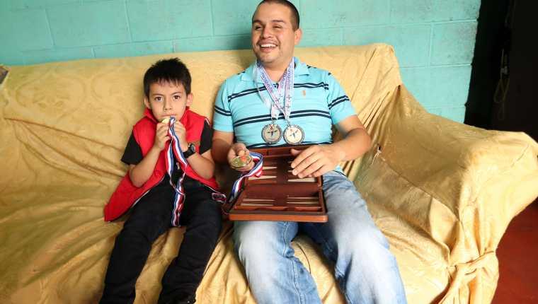 Brayan, junto a su hijo Matías, recordando sus triunfos en el deporte. (Foto Prensa Libre: Jeniffer Gómez)