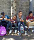 Migrantes hondureños descansan en el Anillo Periférico para desayunar. (Foto Prensa Libre: Edwin Pitán).