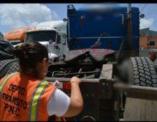 Una agente del departamento de Tránsito coloca una cinta reflectiva  en un cabezal. (Foto Prensa Libre:  cortesía Tránsito)