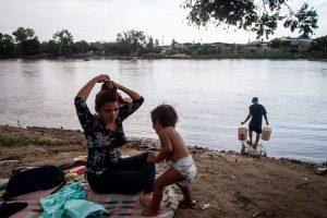 Una mujer hondureña y su hija esperan en la orilla del río para continuar su viaje. Foto Prensa Libre: AFP