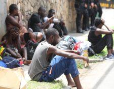 Inmigrantes descansan en la vía pública frente al albergue de Migración, en zona 5, custodiados de policías. (Foto Prensa Libre: Esbin García)
