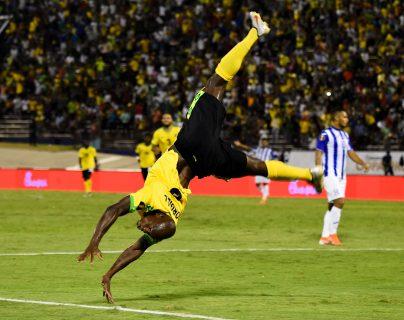 El ariete jamaiquino Dever Orgill celebra de forma acrobática el segundo gol que le marcó a los hondureños (Foto Prensa Libre: AFP)