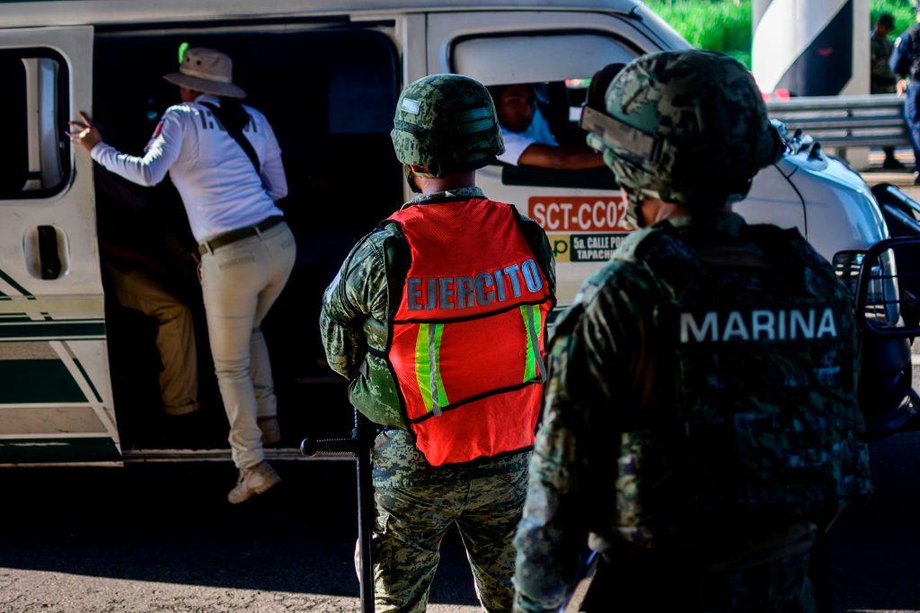 Un agente de inmigración mexicano verifica los documentos en un punto de control en las afueras de Tapachula, estado de Chiapas, México. Foto Prensa Libre: AFP