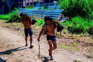 Algunas personas traen de Guatemala materiales de construcción hacia México. Foto Prensa Libre: AFP