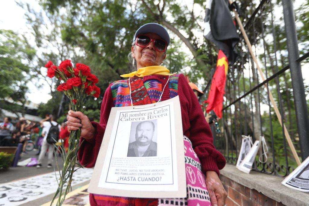 Las personas mostraron varias fotografías de las personas que desaparecieron durante la época del enfrentamiento. Foto Prensa Libre: Óscar Rivas