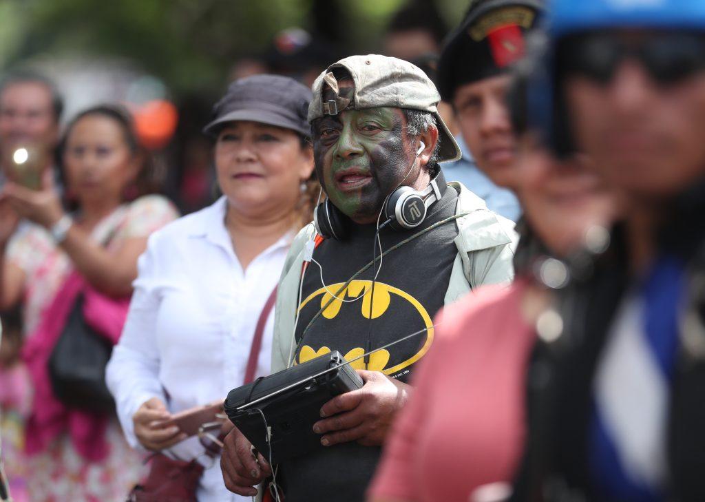 Con el rostro pintado, personas esperan el paso del desfile en la Avenida Reforma. Foto Prensa Libre: Esbin García