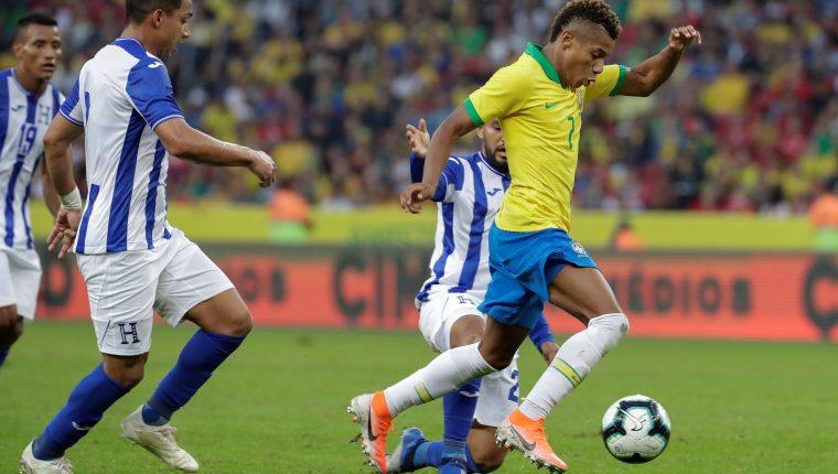 El jugador David Neres (derecha) de Brasil disputa el balón con Jorge Alvarez (i) de Honduras. El atacante es una de las nuevas figuras para Tite. (Foto Prensa Libre: EFE)
