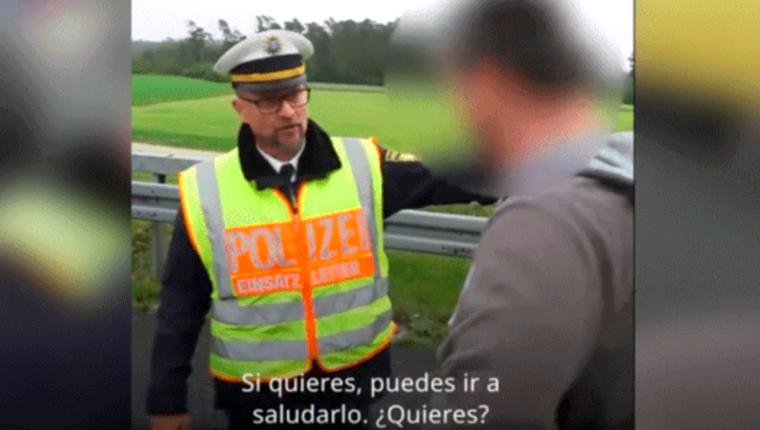 Un conductor escucha atento mientras un policía lo regaña por tomar fotografía de un accidente de tránsito. (Foto Prensa Libre: Captura de video)