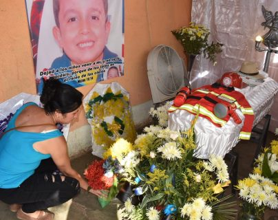 Wendy González coloca flores a un costado del ataúd de su hijo. (Foto Prensa Libre: Mario Morales).