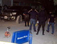 Investigadores reúnen indicios en el lugar donde murió baleado el empresario Erick Castañeda, en Puerto Barrios. (Foto Prensa Libre: Dony Stewart).