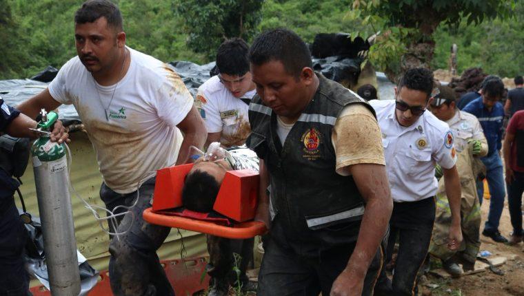 Bomberos trasladan a uno de los trabajadores que quedaron soterrados cuando hacían una zanja en Santa Catarina Pinula. (Foto Prensa Libre: @BVoluntariosGT).