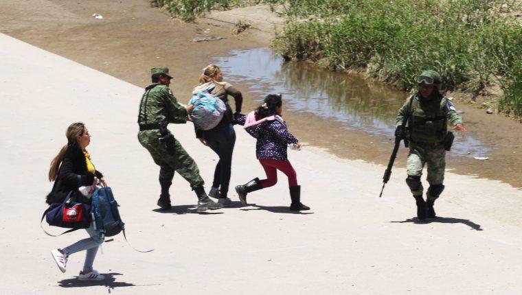 Soldados mexicanos detienen a dos mujeres y a una niña en la frontera de Ciudad Juárez. (Foto Prensa Libre: AFP)