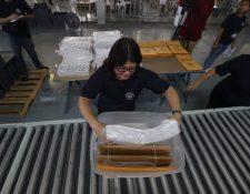 Personal del TSE trabaja en el embalaje de papeletas y enseres que serán utilizados para el voto en EE. UU. (Foto Prensa Libre: Óscar Rivas)