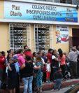 Unas 200 personas se aglomeran en el colegio Ineecc, en zona 1, para recibir bolsas de alimentos. (Foto Prensa Libre: Carlos Hernández)
