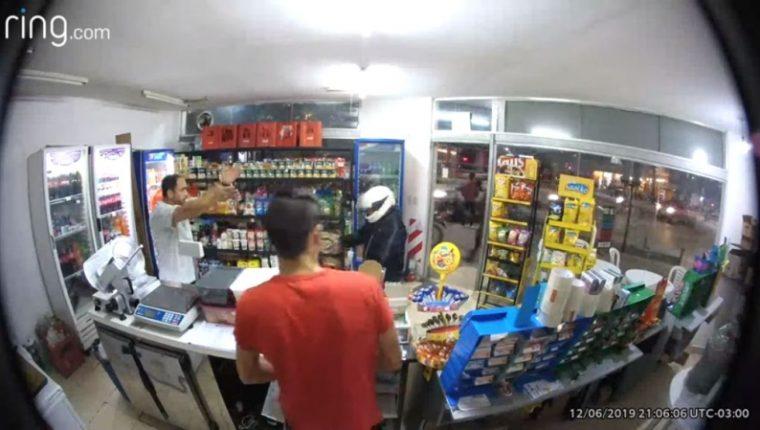 Imagen captada por la cámara de la tienda, en la que se observa al asaltante, con casco blanco, momentos antes de dispararse en la ingle. (Foto del sitio www.t13.cl)
