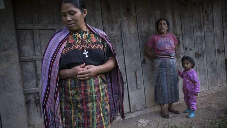 Catarina Mejía (izq.) e Isabel Torres, frente al taller, que lleva años abandonado, de la aldea donde se guardan los repuestos y las piezas para dar mantenimiento a los paneles fotovoltaicos.