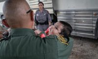 MCALLEN, TEXAS - JULY 02: A U.S. Border Patrol agents briefly holds an infant after she and her mother were taken into custody by U.S. Border Patrol agents on July 02, 2019 in McAllen, Texas. The immigrants, mostly families from Central America, had rafted across the Rio Grande from Mexico to seek political asylum in the United States. They were to be transported by bus to a Border Patrol processing center.   John Moore/Getty Images/AFP == FOR NEWSPAPERS, INTERNET, TELCOS & TELEVISION USE ONLY ==