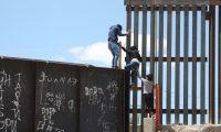 Un grupo de personas tratan de saltar el muro para entrar a territorio estadounidense este lunes, desde el puente negro, en la línea fronteriza de Ciudad Juárez. (Foto Prensa Libre EFE)
