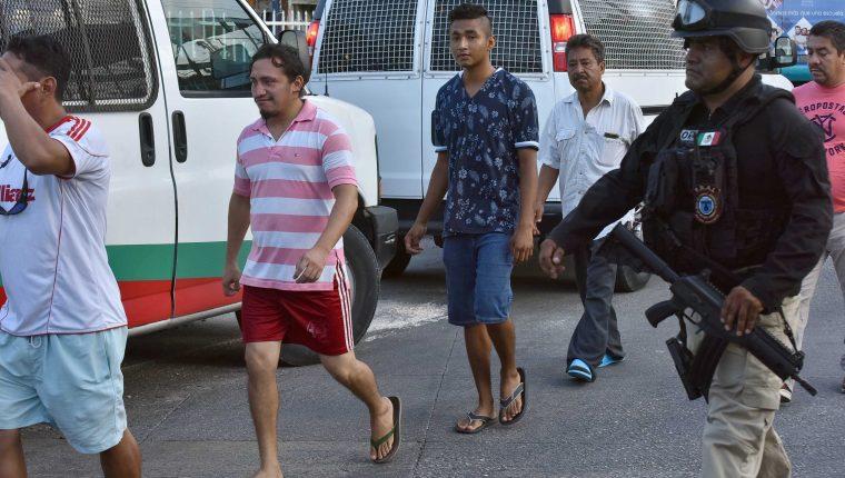 Agentes de la Policía Ministerial, apoyados por la Guardia Nacional, aseguran a 54 migrantes de nacionalidad centroamericana, este martes en la ciudad de Cancún, Quintana Roo . (Foto Prensa Libre: EFE)