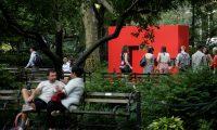 """AME5293. NUEVA YORK (ESTADOS UNIDOS), 10/07/2019.- Transeúntes observan la obra """"Rojo"""", de la primera gran exposición de esculturas exteriores de la minimalista cubana Carmen Herrera, este miércoles, en Nueva York (EE.UU.). La artista cubana Carmen Herrera pasó desapercibida hasta hace poco más de una década, pero este miércoles ha alcanzado una nueva meta, a sus 104 años, al exhibirse un grupo de sus esculturas de gran tamaño en los jardines del Ayuntamiento de Nueva York. """"Me encanta que por fin se la esté reconociendo y que se la esté viendo como una figura artística histórica"""", comentó a Efe Palmer. La exhibición, titulada """"Estructuras Monumentales"""" y que está formada por cinco coloridas grandes piezas de aluminio de líneas rectas, está expuesta en pleno centro de Manhattan, a la vista de los más de ocho millones de habitantes de Nueva York, ciudad considerada el epicentro mundial del arte. EFE/ Kena Betancur"""