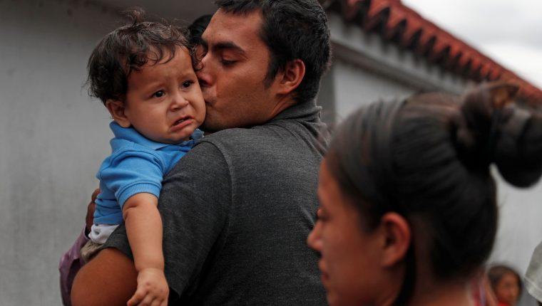 Kevin, migrante guatemalteco recién deportado de Estados Unidos, besa a su hijo Osaías, de 1 año, después de permanecer fuera del país por dos meses, tras su llegada junto a un grupo de migrantes también deportados a Guatemala. (Foto Prensa Libre: EFE)