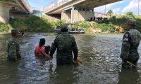MEX8123. MATAMOROS (MÉXICO), 23/07/2019.- Miembros de la Guardia Nacional persuaden a una familia de migrantes de origen guatemalteco para que no crucen el caudal del Río Bravo este martes, en el punto fronterizo del Puente Nuevo, en Matamoros, estado de Tamaulipas (México). La promesa de la Patrulla Fronteriza de recibirlos para saber de su petición de asilo, logró que la familia, compuesta por dos infantes, saliera del río y cruzara sobre el puente donde ya los esperaba un grupo del departamento migratorio estadounidense para ingresarlos de forma segura a territorio norteamericano. Es una vista más de las que se están dando con continuidad y casi a diario en los afluentes del río Bravo, mudo testigo que arrastra a diario historias de sueños y vidas, a pesar de los riegos que representa. EFE/ Marco Rodríguez