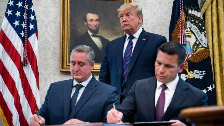 Enrique Degenhart y Kevin McAleenan firman el acuerdo, ante la mirada de Donald Trump. (Foto Prensa Libre: EFE)