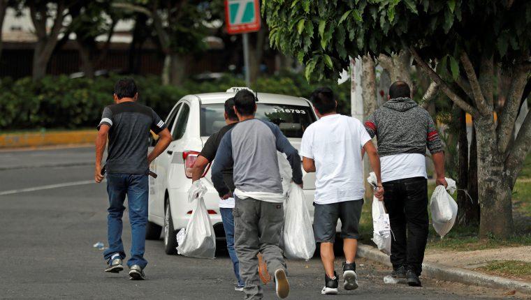 Un grupo de migrantes sale de las instalaciones de la Fuerza Aérea Guatemalteca con sus pertenencias en bolsas plásticas luego de ser deportados de los Estados Unidos. (Foto Prensa Libre: EFE)