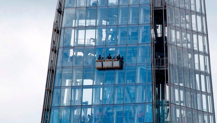 Varias personas limpian las ventanas  del rascacielos The Shard, el más grande de Europa. (Foto Prensa Libre: AFP)