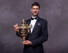 El serbio Novak Djokovic luce muy emocionado el trofeo de Wimbledon. (Foto Prensa Libre: AFP)