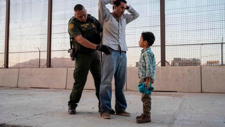 Un padre con su hijo son revisados por un guardia de la Patrulla Fronteriza. (Foto Prensa Libre: AFP)