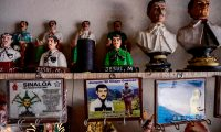 """A key holder bearing a picture of Mexican drug lord Joaquin """"El Chapo"""" Guzman, is displayed for sale below busts of narco-saint Jesus Malverde, at a store next to his chapel in Culiacan, Sinaloa state in northwest Mexico, on July 16, 2019. - An air of sarcasm travels through Sinaloa, birthplace of the legendary Mexican drug lord Joaquin """"El Chapo"""" Guzman, before the imminent sentence of life imprisonment that he will receive this Wednesday in the United States. Inhabitants of this arid region who consider him their benefactor assure that neither the violence nor drug trafficking will diminish. (Photo by Pedro PARDO / AFP)"""