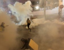 Los manifestantes huyen del gas lacrimógeno disparado por la policía después de una marcha contra un polémico proyecto de ley de extradición en Hong Kong. (Foto Prensa Libre: AFP)