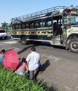 Usuarios permanecen junto a bus que fue objeto de asalto en la Autopista Palín-Escuintla. (Foto Prensa Libre: Enrique Paredes).