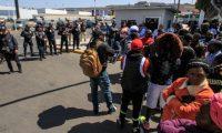 """AME4878. TIJUANA (MÉXICO), 09/07/2019.- Alrededor de 200 migrantes de Haití y de varios países de África participan en una manifestación en la que denunciaron presuntos abusos de las autoridades mexicanas este martes, frente al cruce internacional """"El Chaparral"""", frontera con Estados Unidos, en Tijuana (México). Ante la sede del Instituto Nacional de Migración (INM) de México situado en los alrededores del cruce, los migrantes exigían respuesta a sus quejas, entre las que sobresalía la denuncia de una cuota económica para ser anotados en listas de esperar por parte de autoridades mexicanas. EFE/ Joebeth Terriquez"""