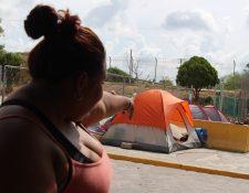 La migrante hondureña Melissa Aldana muestra las tiendas de campaña donde esperan algunos migrantes, en Matamoros, México. (Foto Prensa Libre: EFE).