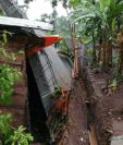 La lluvia ocasionó el colapso de un muro en El Asintal, Retalhuleu. (Foto Prensa Libre: Conred).