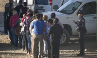 EL PASO, TEXAS - JUNE 02: Migrants wait to be processed and loaded onto a bus by United States Customs and Border Protection agents after being detained when they crossed illegally into the United States from Mexico on June 02, 2019 in El Paso, Texas. The location is in an area where migrants frequently turn themselves in to Border Patrol and ask for asylum after crossing the border. In recent months, U.S. immigration officials have seen a surge in the number of asylum seekers arriving at the border.   Joe Raedle/Getty Images/AFP == FOR NEWSPAPERS, INTERNET, TELCOS & TELEVISION USE ONLY ==