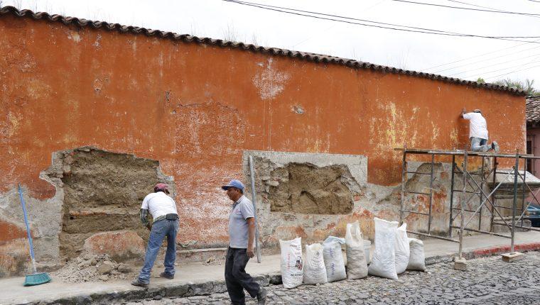 Trabajadores del CNPAG retiran repello dañado de uno de los inmuebles intervenidos en el barrio Escuela de Cristo de Antigua Guatemala. (Foto Prensa Libre: Julio Sicán)