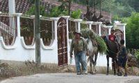 Un hombre camina por una calle de la aldea El Quebracho, frente a un vivienda inhabitada, como muchas en la comunidad de las cuales las familias se fueron a EE. UU. (Foto Prensa Libre: Esbin García)